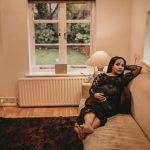 woman sitting on brown sofa near white radiator panel under glass window