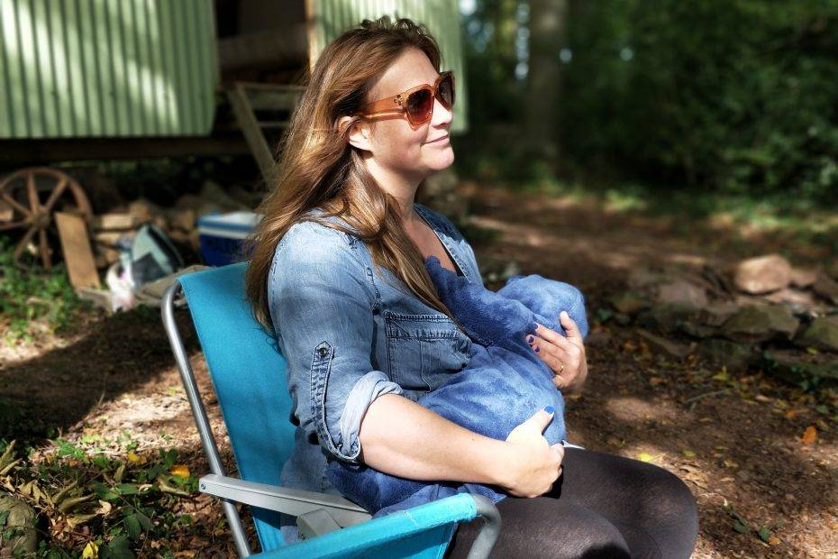 woman carrying baby while sitting on chair