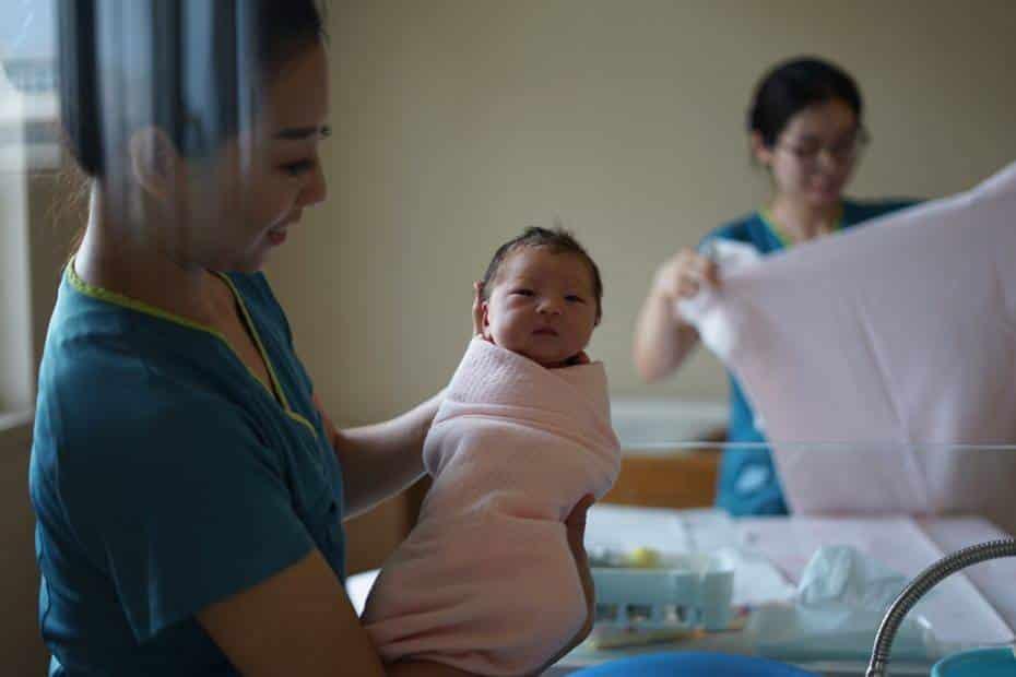 woman carrying newborn baby